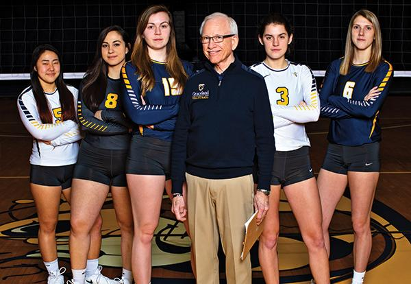 Coach Stew McDole with five girls from the women's volleyball team standing on the Closson Gym center court